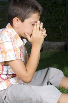 Free Young Boy Praying Outdoors Stock Image - 6092701