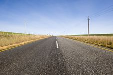 Deserted Country-road Running Through Green Fields Royalty Free Stock Photo
