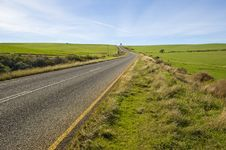 Deserted Country-road Running Through Green Fields Royalty Free Stock Photography
