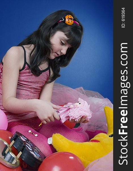 Young and beautiful girl playing with her doll