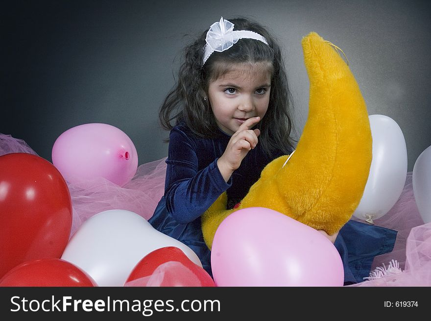 Sweet young girl playing with her plush moon