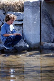 Boy Spotting Trout In Water Stock Photo