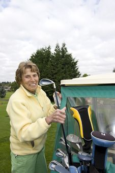 Female Golfer With Cart Stock Photo