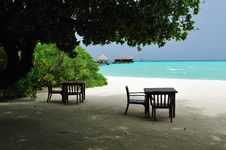 Couple Of Tables And Chairs On A Sandy Beach Stock Image