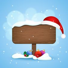 Wooden Sign With Christmas Hat And Baubles In The Snow Royalty Free Stock Photography