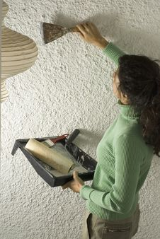 Woman Scrapes Wall While Painting - Vertical Stock Photo