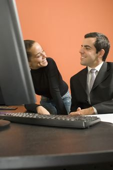 Businessman And Woman By Computer - Vertical Stock Photography