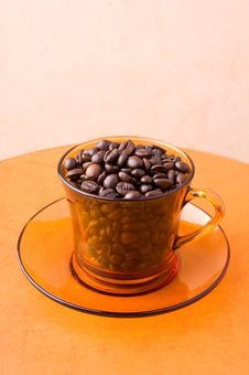 Orange Cup With Coffee Beans Royalty Free Stock Photos