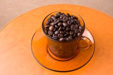 Orange Cup With Coffee Beans Stock Photography