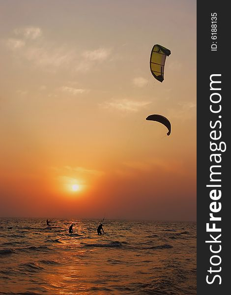 Silhouettes of kite surfers