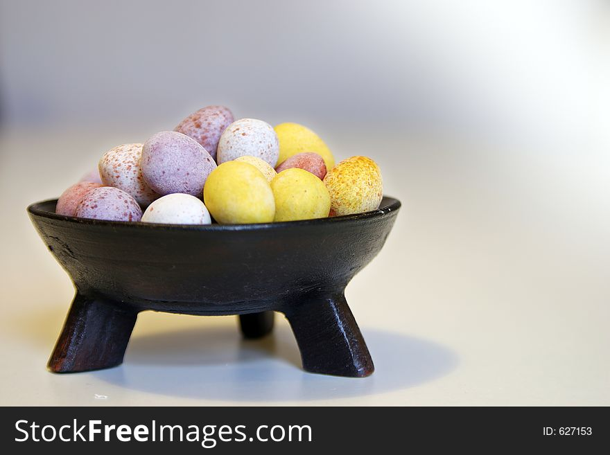 Mini candy chocolate eggs in a decorative tripod dish