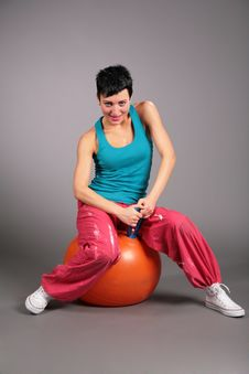 Young Woman In Sportswear Sits On Orange Ball Stock Photo