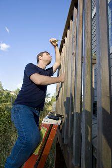 Free Man Repairing Siding - Vertical Stock Images - 6201804