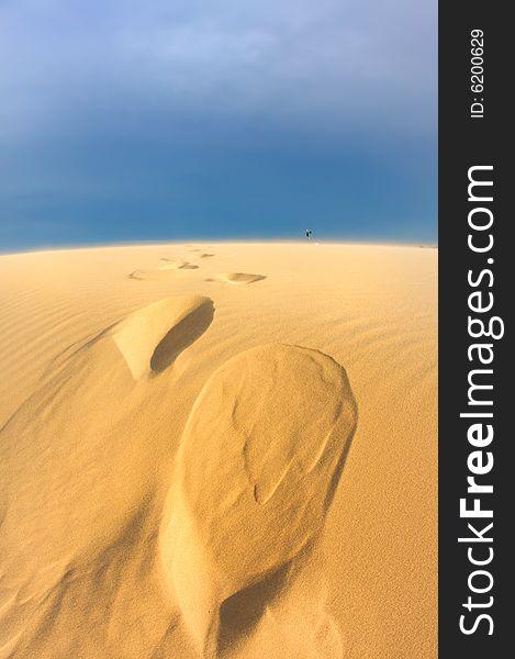 Windswept sand dunes on a blue sky