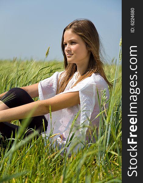 Sadness girl sitting on grass