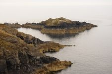 Weathered Rocks Stretching Out In The Sea Stock Photo
