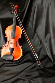 Violin And Bow On Black Silk Stock Image