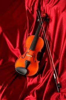Violin And Bow On Red Silk Stock Photography