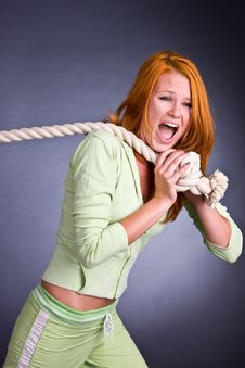 The Young Woman In A Sports Suit Pulls A Rope Stock Photo