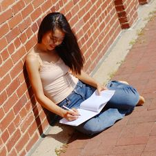 Girl Writing In Note Book Royalty Free Stock Photo
