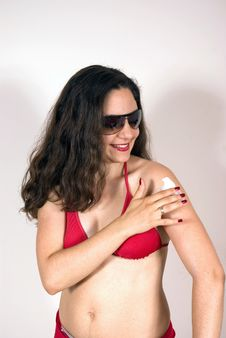 Girl In Swim Suit Putting Sunscreen Lotion Stock Image