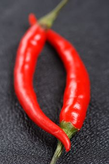 Free Two Red Chillies On Black Leather Background, Stock Image - 6289511