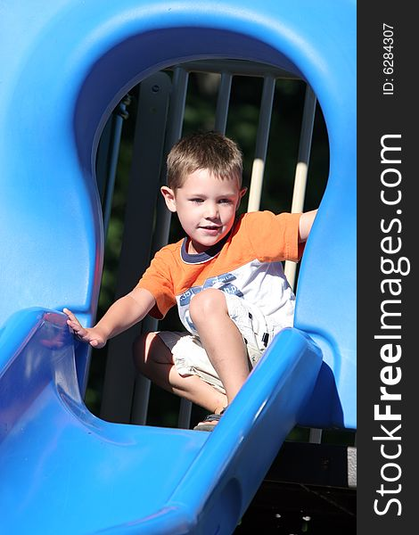 Young boy at the top of a shiny blue slide