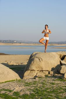 A Young Woman On Top Of A Rock Doing Yoga Royalty Free Stock Photo