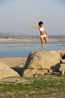A Young Woman On Top Of A Rock Doing Yoga Stock Photo