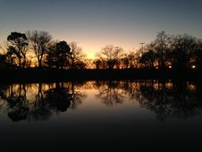 Free Trees Reflecting In Water Surface During Sunset In Winter. Royalty Free Stock Photos - 63329478