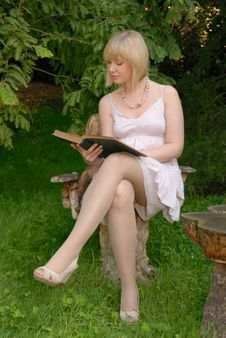 Cute Blond Reads Book In Garden Stock Photos
