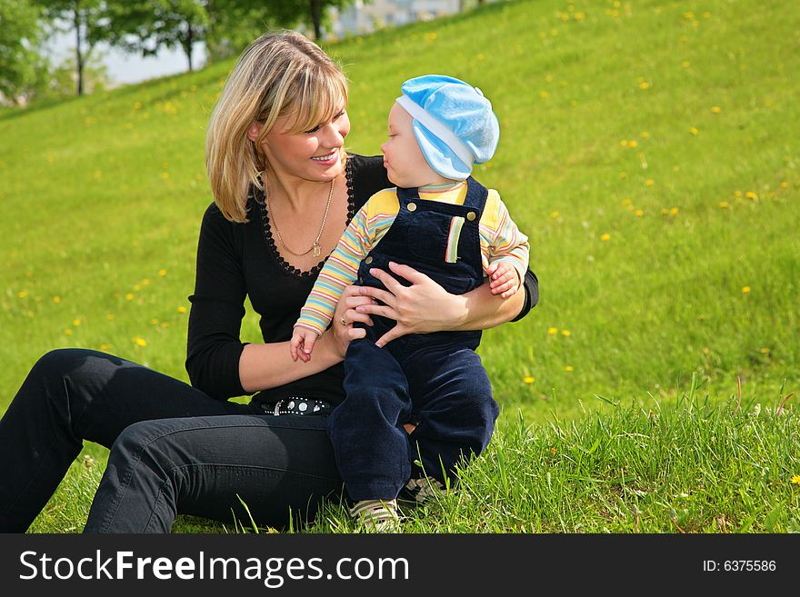 Mother with baby sit on grass