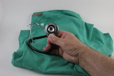 Hand Holding Stethoscope Over Smock. Stock Images
