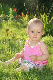 Baby Girl Sitting On The Grass Stock Photo