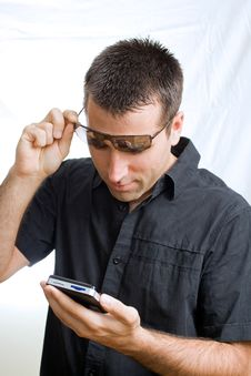 Free Young Man In Sunglasses Looking At His Cellphone Royalty Free Stock Images - 6436079