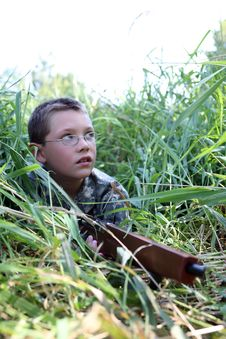 Free Child In Grass Holding Toy Rifle Royalty Free Stock Photography - 6437497