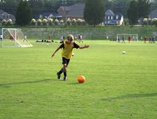 Boy Kicking A Ball On The Field. Stock Photos