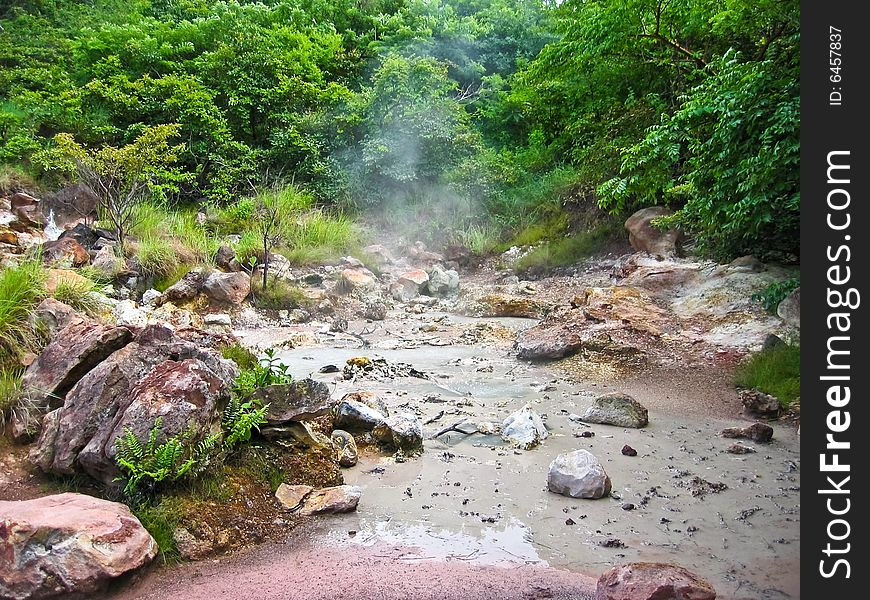 Volcanic mud pool with bubbles in a green environment