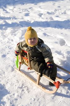 Baby In Green Coat  Sitting In Sled Stock Images