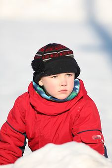 Boy In Snowsuit And Hat Sitting In A Snowbank Royalty Free Stock Photography