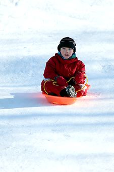 Boy In Red In Sled Going Downhill Royalty Free Stock Photography