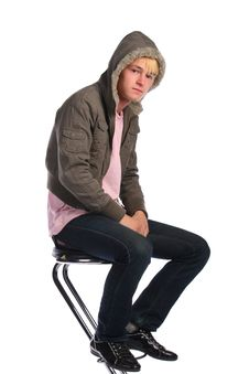 Young Man In Jacket With Fur Sits On Stool Stock Photos