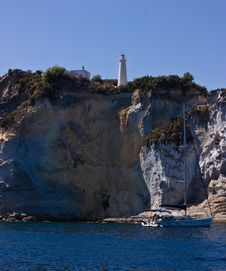 Lighthouse On Steep Mountain And Sail Yacht Stock Images