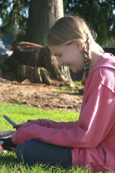 Girl Texting In The Park Stock Photo