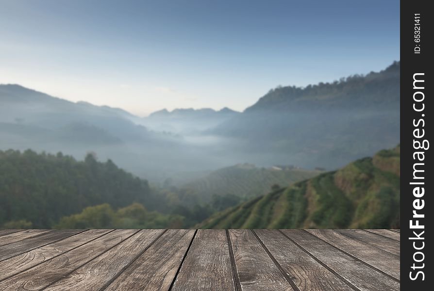 Wooden table and the tea plantations background