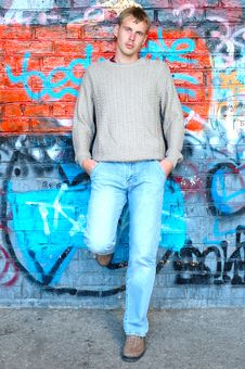 Free Young Stylish Man Stand Near Graffiti Brick Wall. Stock Image - 6582611
