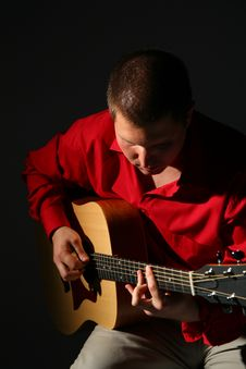 Guitarist In Red Shirt Royalty Free Stock Photography