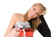 Beautiful Girl Looks At The Camera With Red Gift Royalty Free Stock Image