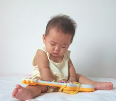 Free Lovely Baby And Toy Guitar Stock Photography - 6616682