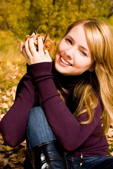 Pretty Girl With Yellow Leaves In Her Hands Royalty Free Stock Photography